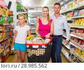 family of three choosing food in the grocery shop. Стоковое фото, фотограф Яков Филимонов / Фотобанк Лори