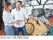 Купить «Man with woman talking about bicycles with characteristic», фото № 28985622, снято 14 мая 2018 г. (c) Яков Филимонов / Фотобанк Лори