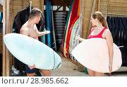 Купить «Young couple planning to surf, choosing boards and surfing suits in beach club», фото № 28985662, снято 30 апреля 2018 г. (c) Яков Филимонов / Фотобанк Лори