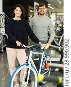 Купить «Smiling couple standing with sport bicycle», фото № 28990902, снято 8 января 2018 г. (c) Яков Филимонов / Фотобанк Лори
