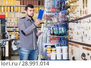 serious man customer examining various glue tubes in store. Стоковое фото, фотограф Яков Филимонов / Фотобанк Лори