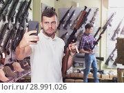 Купить «Man taking selfie with weapon», фото № 28991026, снято 4 июля 2017 г. (c) Яков Филимонов / Фотобанк Лори