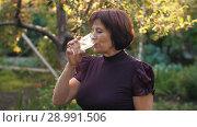 Купить «Elderly woman drinking water», видеоролик № 28991506, снято 26 августа 2018 г. (c) Илья Шаматура / Фотобанк Лори
