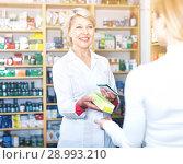 Купить «Mature female seller suggesting care products to young customer», фото № 28993210, снято 15 марта 2017 г. (c) Яков Филимонов / Фотобанк Лори