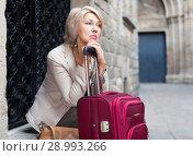 Купить «Mature female tourist is sitting with suitcase», фото № 28993266, снято 3 сентября 2017 г. (c) Яков Филимонов / Фотобанк Лори
