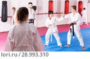 Купить «Kids in kimonos exercising techniques in pair during taekwondo class at gym», фото № 28993310, снято 6 августа 2018 г. (c) Яков Филимонов / Фотобанк Лори