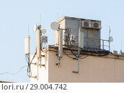 Купить «Антенны базовой станции оператора сотовой связи на крыше здания», фото № 29004742, снято 28 августа 2018 г. (c) Алексей Букреев / Фотобанк Лори