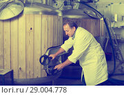 Brewer is controls the brewing process near reservoir with beer. Стоковое фото, фотограф Яков Филимонов / Фотобанк Лори