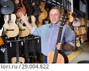 Купить «Mature man choosing acoustic guitar», фото № 29004822, снято 18 сентября 2017 г. (c) Яков Филимонов / Фотобанк Лори