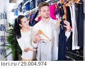 Купить «Laughing couple deciding on new sportswear», фото № 29004974, снято 22 ноября 2016 г. (c) Яков Филимонов / Фотобанк Лори