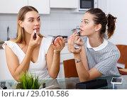 Купить «Two positive young female friend doing make up at table with cosmetics», фото № 29010586, снято 2 августа 2018 г. (c) Яков Филимонов / Фотобанк Лори