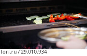 Купить «Cook puts sliced cucumber plates next to pieces of red pepper in the oven», видеоролик № 29010934, снято 17 января 2019 г. (c) Константин Шишкин / Фотобанк Лори