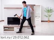 Купить «Man trying to fix broken tv», фото № 29012062, снято 9 марта 2018 г. (c) Elnur / Фотобанк Лори