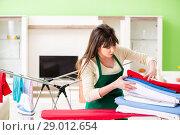 Купить «Young woman ironing clothing at home», фото № 29012654, снято 29 мая 2018 г. (c) Elnur / Фотобанк Лори