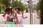 Купить «women with shopping bags looking at shop window», видеоролик № 29020634, снято 15 августа 2018 г. (c) Syda Productions / Фотобанк Лори