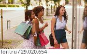Купить «women with shopping bags looking at shop window», видеоролик № 29020654, снято 15 августа 2018 г. (c) Syda Productions / Фотобанк Лори
