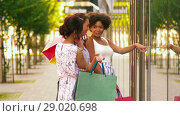 Купить «women with shopping bags looking at shop window», видеоролик № 29020698, снято 15 августа 2018 г. (c) Syda Productions / Фотобанк Лори