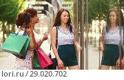 Купить «women with shopping bags looking at shop window», видеоролик № 29020702, снято 15 августа 2018 г. (c) Syda Productions / Фотобанк Лори