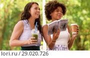 Купить «women with city guide and drinks on street», видеоролик № 29020726, снято 15 августа 2018 г. (c) Syda Productions / Фотобанк Лори