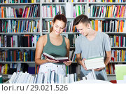 Купить «portrait of teenage boy and girl customers looking at open book standing among bookshelves», фото № 29021526, снято 16 сентября 2016 г. (c) Яков Филимонов / Фотобанк Лори