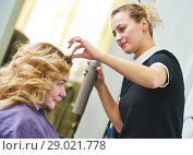 Купить «hairdo in beauty salon. hairdresser fixing hair with hairspray», фото № 29021778, снято 28 марта 2017 г. (c) Дмитрий Калиновский / Фотобанк Лори