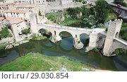 Купить «Aerial view of historic centre of Besalu with Romanesque bridge over Fluvia river, Catalonia, Spain», видеоролик № 29030854, снято 12 июня 2018 г. (c) Яков Филимонов / Фотобанк Лори