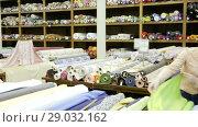 Купить «Young woman looking for interesting cloth in textile shop», видеоролик № 29032162, снято 28 марта 2018 г. (c) Яков Филимонов / Фотобанк Лори