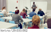 Купить «Smiling African American teacher giving presentation for students in lecture hall», видеоролик № 29033002, снято 23 мая 2018 г. (c) Яков Филимонов / Фотобанк Лори