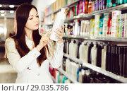 Serious young female choosing hair care products at cosmetics showroom. Стоковое фото, фотограф Яков Филимонов / Фотобанк Лори