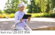 Купить «senior woman with tablet pc at summer park», видеоролик № 29037954, снято 21 августа 2018 г. (c) Syda Productions / Фотобанк Лори