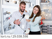Купить «Young couple customers trying use desk lamp in store», фото № 29038598, снято 29 января 2018 г. (c) Яков Филимонов / Фотобанк Лори