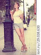 Купить «Girl near lamp post using phone to find address», фото № 29038630, снято 15 августа 2017 г. (c) Яков Филимонов / Фотобанк Лори