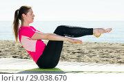 Купить «Woman training yoga poses on beach», фото № 29038670, снято 8 мая 2017 г. (c) Яков Филимонов / Фотобанк Лори