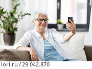 Купить «senior woman taking selfie by smartphone at home», фото № 29042870, снято 24 мая 2018 г. (c) Syda Productions / Фотобанк Лори