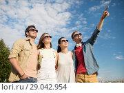 Купить «happy friends looking at something outdoors», фото № 29042954, снято 7 июля 2018 г. (c) Syda Productions / Фотобанк Лори