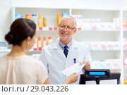 Купить «senior apothecary with prescription at pharmacy», фото № 29043226, снято 27 июня 2015 г. (c) Syda Productions / Фотобанк Лори