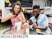 Купить «mixed race couple photographing wok at food truck», фото № 29043278, снято 1 августа 2017 г. (c) Syda Productions / Фотобанк Лори