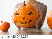 Купить «close up of woman with halloween pumpkin at home», фото № 29043290, снято 15 сентября 2017 г. (c) Syda Productions / Фотобанк Лори