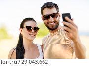 Купить «happy couple taking selfie by smartphone in summer», фото № 29043662, снято 15 июля 2018 г. (c) Syda Productions / Фотобанк Лори