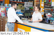 Купить «Cheerful girl seller helping male customer at the counter», фото № 29043774, снято 17 мая 2018 г. (c) Яков Филимонов / Фотобанк Лори