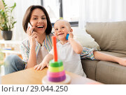 Купить «mother calling phone and baby boy playing at home», фото № 29044250, снято 12 мая 2018 г. (c) Syda Productions / Фотобанк Лори