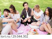 Купить «friends with camera photographing at summer picnic», фото № 29044302, снято 17 июня 2018 г. (c) Syda Productions / Фотобанк Лори