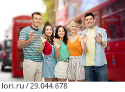 happy friends showing ok over london city street. Стоковое фото, фотограф Syda Productions / Фотобанк Лори