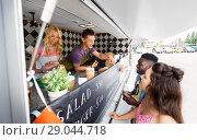 Купить «customers and seller pointing at food truck menu», фото № 29044718, снято 1 августа 2017 г. (c) Syda Productions / Фотобанк Лори