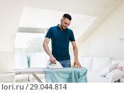 Купить «man ironing shirt by iron at home», фото № 29044814, снято 10 мая 2018 г. (c) Syda Productions / Фотобанк Лори