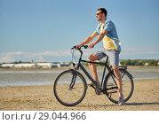 Купить «happy man riding bicycle along summer beach», фото № 29044966, снято 23 июля 2017 г. (c) Syda Productions / Фотобанк Лори