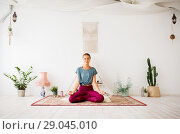 Купить «woman meditating in lotus pose at yoga studio», фото № 29045010, снято 21 июня 2018 г. (c) Syda Productions / Фотобанк Лори