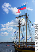 Купить «Saint Petersburg. A beautiful sailing vessel under the Russian flag in the water area of the Neva River near the pier of the Peter and Paul Fortress takes part in the celebration of the Baltic Yacht Week. August 18, 2018», фото № 29045926, снято 18 августа 2018 г. (c) Виктория Катьянова / Фотобанк Лори