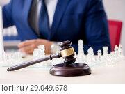 Купить «Young lawyer playing chess to train his court strategy and tacti», фото № 29049678, снято 31 июля 2018 г. (c) Elnur / Фотобанк Лори
