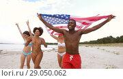 Купить «friends with american flag running on summer beach», видеоролик № 29050062, снято 24 августа 2018 г. (c) Syda Productions / Фотобанк Лори